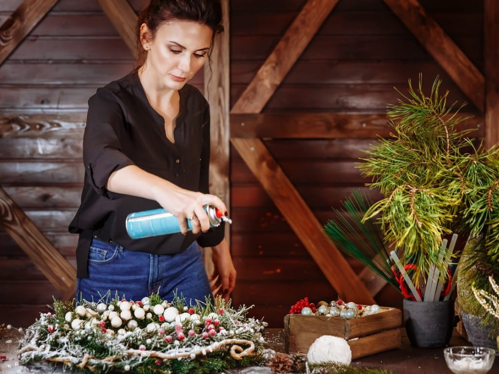 woman spraying wreath with artificial snow