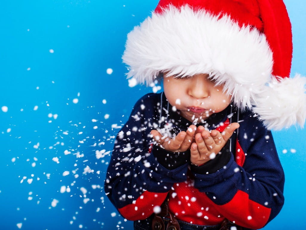 young boy blowing artificial snow out of his hands